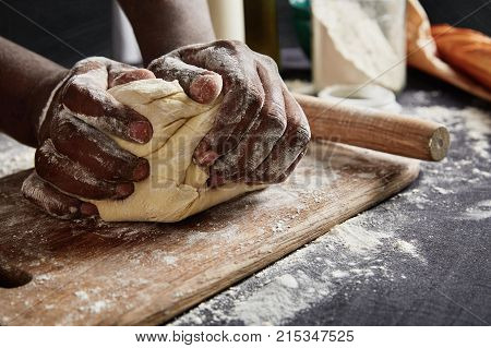 Baking Concept. Hard Working Unrecognizable Black Male Prepares Pastry By Himself, Kneads Dough On W