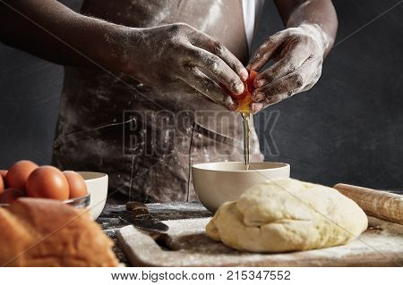 Man`s Hands Break Egg In Bowl As Prepares Pastry. Cropped Shot Of Busy Male Cook Bakes Delicious Cak