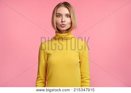 Attractive Light Haired Female Rounds Lips, Wears Yellow Turtleneck Sweater, Looks Directly Into Cam