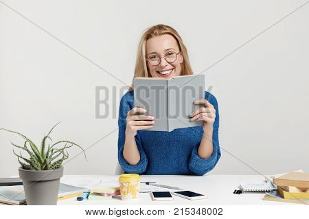 Positive Smiling Woman Sits Over Woking Space, Holds Book, Reads Information, Prepares For Exam Or C