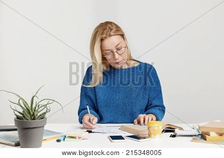 Serious Concentrated Female Student Or Scientific Worker Rewrites Information From Book Into Noteboo