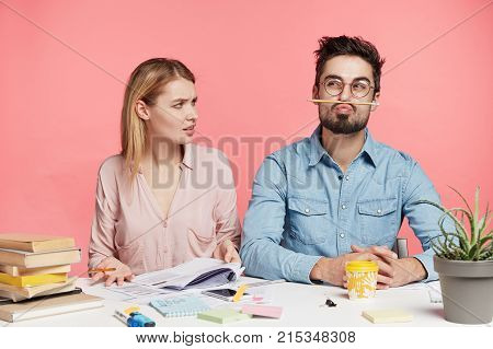 Two Coworkers Busy Making Monthly Sales Report: Funny Bearded Man Being Tired Of Work, Keeps Pencil