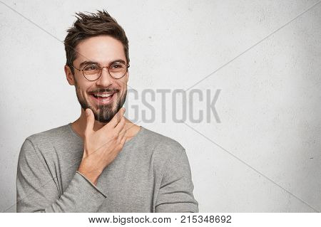 Positive Bearded Thoughtful Male Has Brilliant Idea, Wants To Realize It, Keeps Hand On Chin, Poses