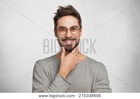 Smiling Male Worker Has Trendy Hairdo, Keeps Hand Under Chin, Wears Casual Clothes And Optical Glass