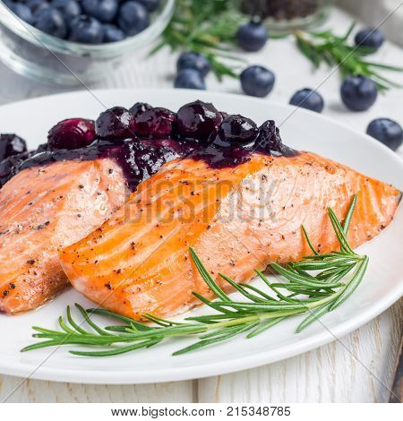 Baked salmon fillet with blueberry and rosmarin sauce on white plate square format