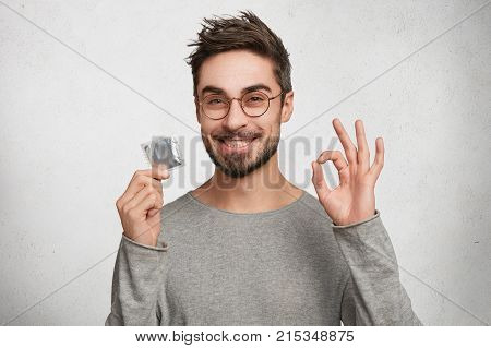 Portrait Of Happy Smiling Male With Bristle Shows Ok Sign As Holds Condomn, Agrees To Spend Night Wi