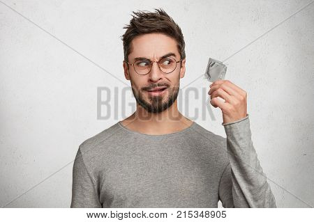 Bearded Stylish Man Holds Comdomn, Looks With Hesitation, Doesn`t Know Whether To Use It And What Qu