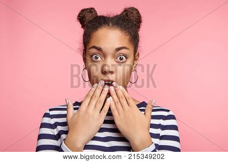 Stupefied Shocked Young Female Has Two Hair Buns Shows Something Dangereous Or Awful, Stares At Came