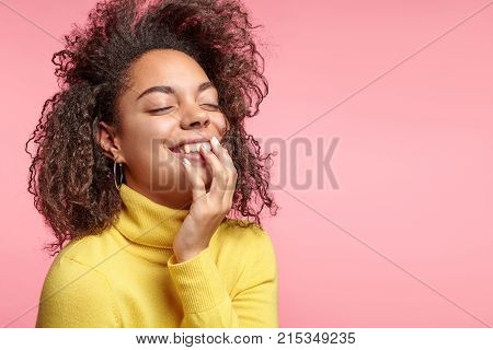 Dreamful African Female Has Cheerful Expression, Closes Eyes In Enjoyment, Wears Yellow Sweater, Gla