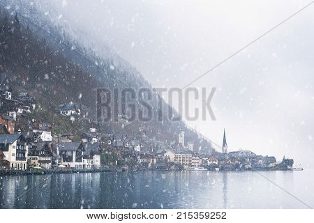 Austrian mountain town under snowfall - Winter weather theme image with the famous Hallstatt market town surrounded by the Alps mountains and the Hallstatter lake on a snowy day of November.