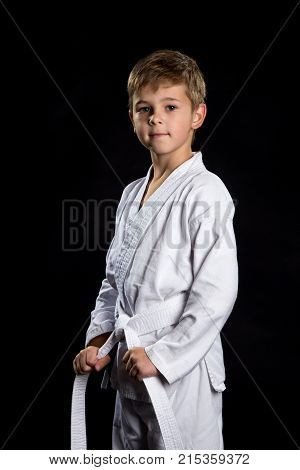 Smiling karate kid in brand new kimono posing on the black background. Karate fighter holding his belt.