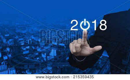 Businessman pressing 2018 start up business icon over modern city tower street and expressway Happy new year concept