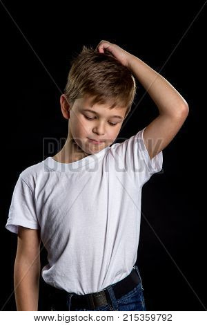 Emotions of children. Regretting child, intelligent boy on the black background with one hand on the head and bowed head.