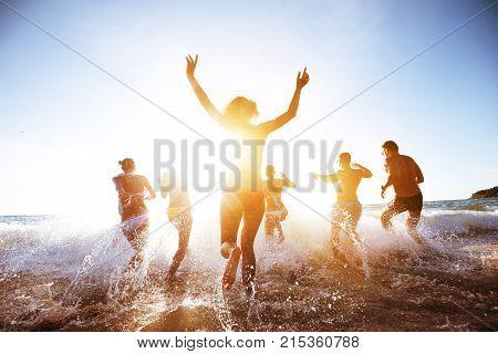 Group of beautiful people having fun, run and jumps at sunset beach