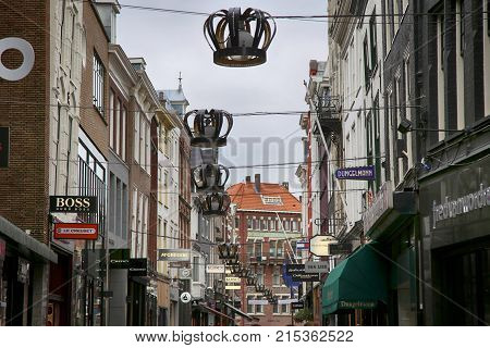 THE HAGUE THE NETHERLANDS - AUGUST 18 2015: View of the Hoogstraat Street in the city center. Shopping street and decorations on the streets with crowns in The Hague Netherlands on August 18 2015.