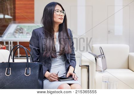 Portrait shot of pensive Asian entrepreneur in formalwear looking away while thinking over promising project, interior of modern boardroom on background