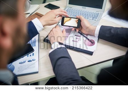 Unrecognizable white collar workers sitting at office desk and watching video on smartphone while taking short break from work
