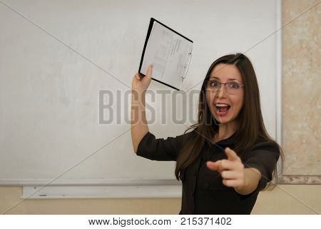 Desperated wicked teacher woman throws a day book into student and showing ahead with her index finger. Education concept.
