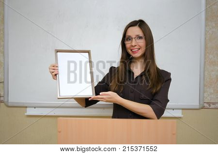 Best teacher. Best student. Award ceremony. Graduate. Young teacher or student holds in hands a diploma or certificate paper sheet in photo frame and with copy space on school board background.