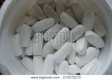 Plastic Tub Filled With White Caplets From Above