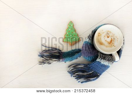 mug with frothy cappuccino wrapped in a blue scarf next to a ginger fir tree top view / warming Christmas coffee break