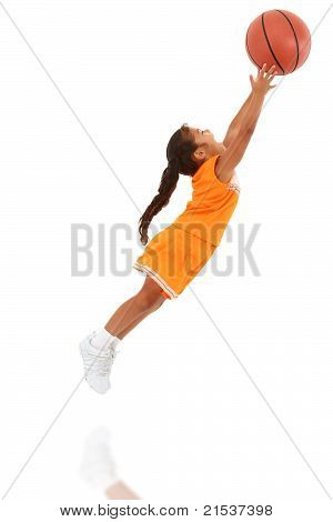 Adorable African-Hispanic Girl Child In Uniform Jumping With Basketball