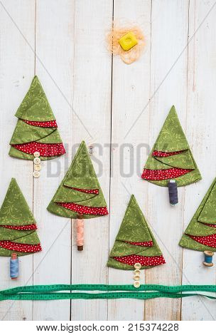 patchwork and tailoring concept - collage of sewing tools and decorative red-and-green napkins on white wooden floor, embroidered towels in shape of trees, applique of thread and buttons, vertical