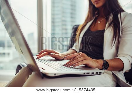 Close-up view of elegant female journalist writing an article using netbook sitting in modern office.