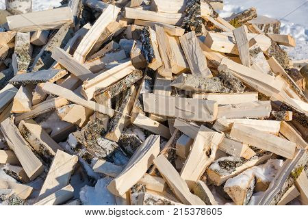 Firewood. A lot of firewood lie in a heap. The split firewood in a heap.