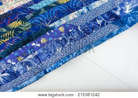 creativity, imagination, handcraft, needlework concept - part of sea blue colored blanket sewed of long thin rags with almost invisible light stitches. with white corner empty space for lettering