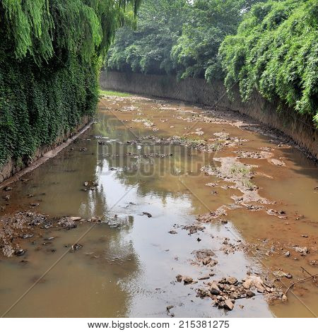 A polluted river in the city. The toxic water flowing out of the sewers.