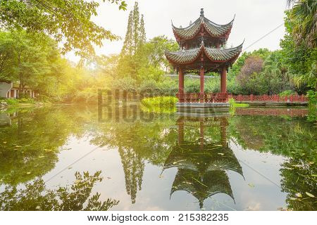Chinese pavilion reflecting in a pond in BaiHuaTan public park, Chengdu, China