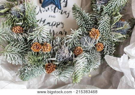 close up of conifer branches with white paints on them, small pinecones that looks like wooden roses, all wreath are wraped in paper