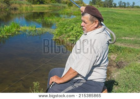 Senior man sitting on a riverside on a wicker stool and scratching his back with walking stick