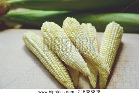 Baby corn with water drop on wooden board