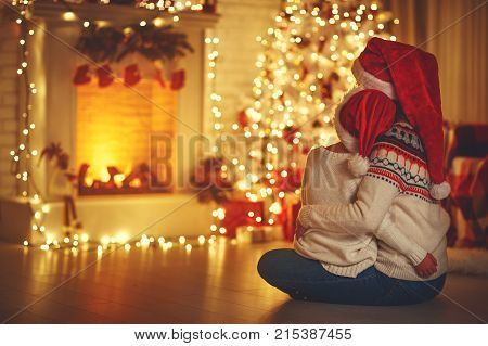 happy family mother and daughter are sitting with their backs near Christmas tree on eve of Christmas