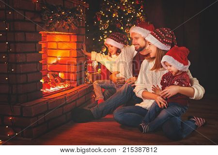 happy family father mother and children sitting by fireplace on Christmas Eve