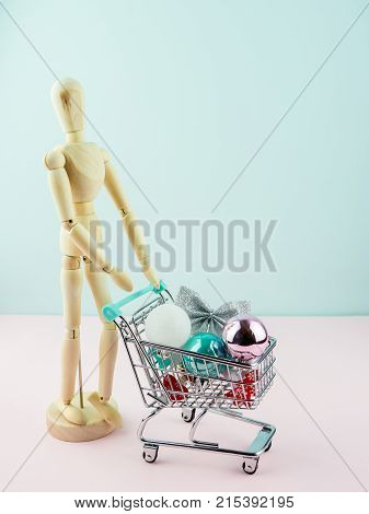 Woden manikin with Christmas decorations in grocery trolley on blue background. minimal christmas shopping concept idea
