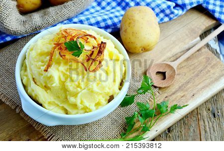 Mashed potatoes or Puree in white bowl with Crisp onion and parsley on wooden background