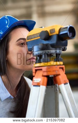 Serious surveyor engineer worker making measuring with theodolite equipment at construction site