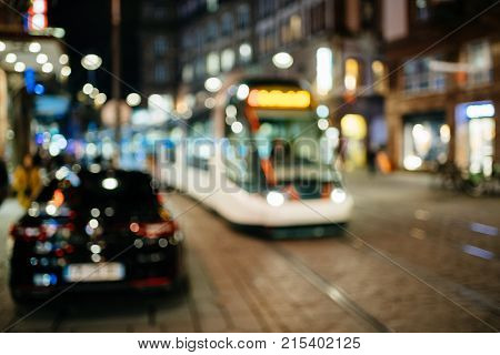 Defocused view of central city of Strasbourg in France with light bokeh and tramway driving on the main street deocrated for Christmas