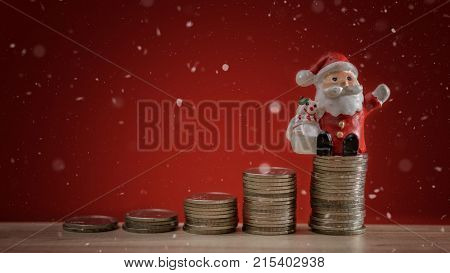 Christmas holiday background with Santa and money coin stack background. Christmas celebration holiday background. Saving money concept. Working in holiday.