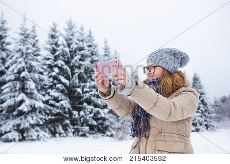 Young woman takes photo on a background of snow-covered winter forest. Snowy weather. Woman taking photo on phone. Girl smiling at the camera. Winter holidays.