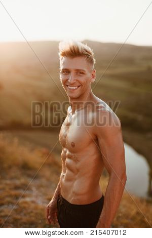 Handsome bare-chested man standing in nature and cheerfully smiling.