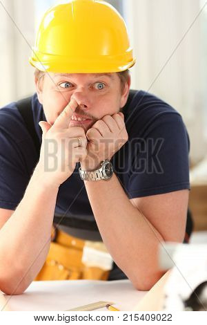 Smiling funny worker in yellow helmet posing with finger in nose. Manual job workplace DIY inspiration improvement fix shop hard hat joinery startup idea industrial education profession career