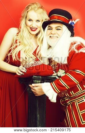 Happy senior man beefeater yeomen warder in uniform and pretty girl young sexy blond woman in dress with crown smile on red wall