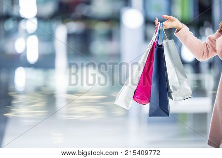 Beautiful Happy Girl With Credit Card And Shopping Bags In Shopping Mall. Shopping Center In The Bac