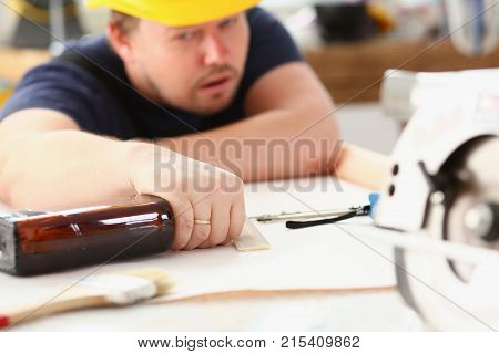 Arm of drunken worker in yellow helmet hold liquor bottle sleeping at table closeup. Manual job workplace DIY inspiration fix shop hard hat industrial education profession career