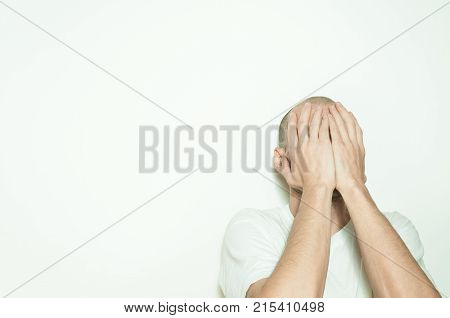 Young depressed man suffering from anxiety and feeling miserable cover his face with his hands and leaning on the white wall