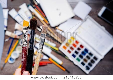on the table are scattered art supplies, colorful watercolor paints, pencils, gouache, tubes with oil paint, the girl holds a brush in her hand